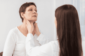 dottoressa esamina tiroide della paziente